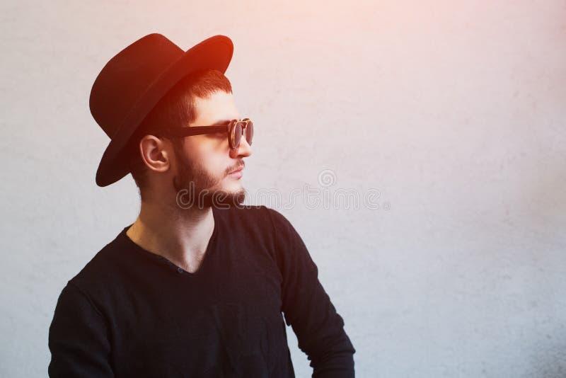 Profielportret van jonge gebaarde kerel, die zonnebril en zwarte hoed over witte achtergrond dragen royalty-vrije stock foto