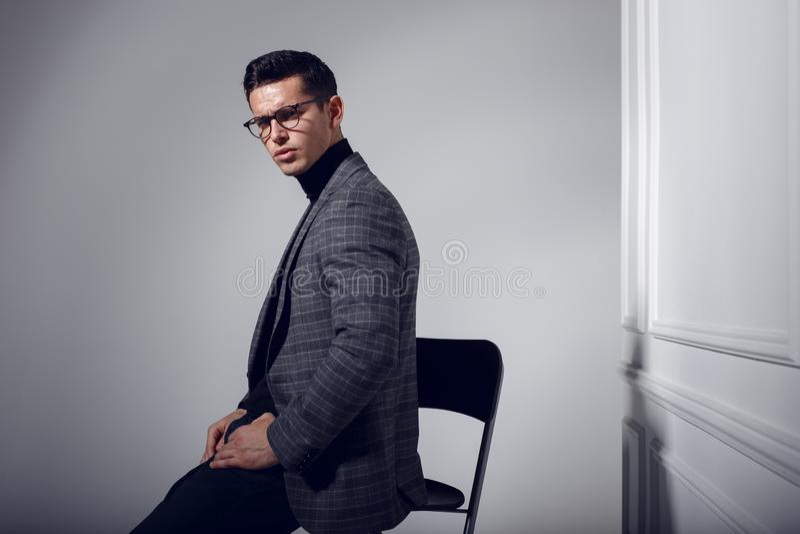 Profielportret van knap, elegant mens in zwart-grijs kostuum en oogglazen, op witte achtergrond stock foto