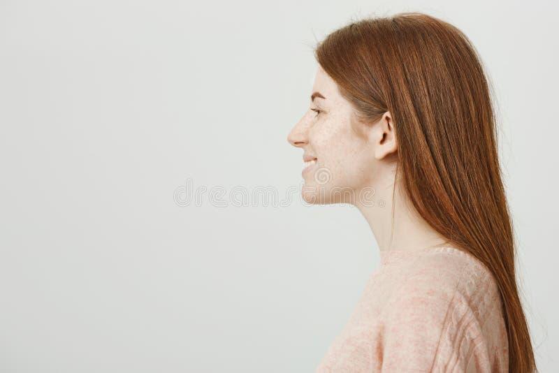 Profielportret van schitterend vrouwelijk roodharigemeisje met sproeten die en zich tegen grijze achtergrond glimlachen bevinden  royalty-vrije stock foto