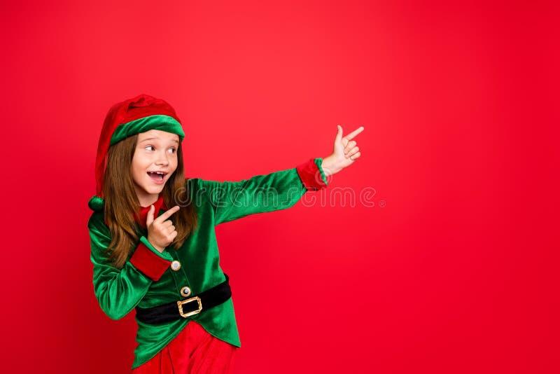 Profielzijfoto van een vrolijke redhead elf met haar wijsvinger advertenties met een wijsvinger om gebeurtenissen aan te bevelen  stock fotografie