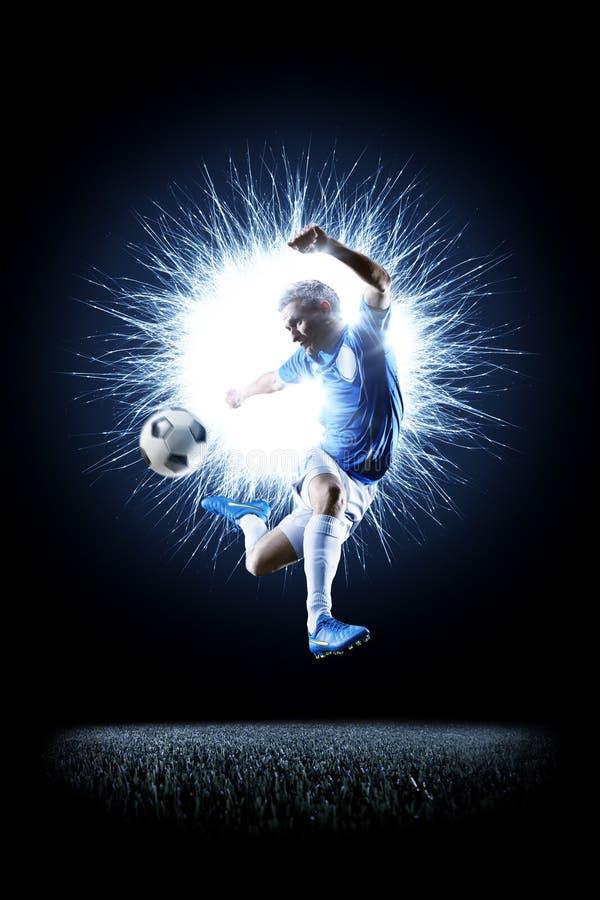 Profifußballfußballspieler in der Aktion auf Schwarzem stockfotografie