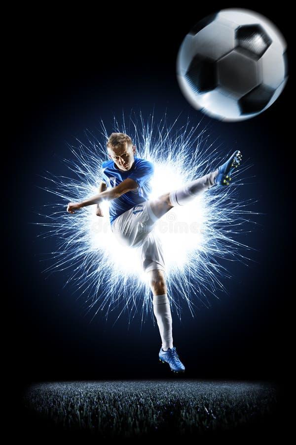 Profifußballfußballspieler in der Aktion auf Schwarzem stockfoto