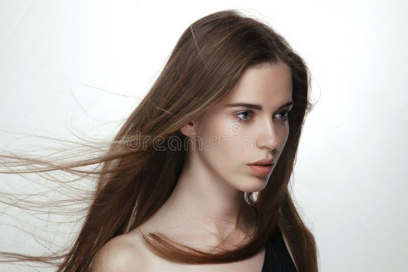 Profil av den härliga sinnliga flickan med långt hår i vind, nakna skuldror, isoated på vit bakgrund Ny skincare royaltyfria bilder