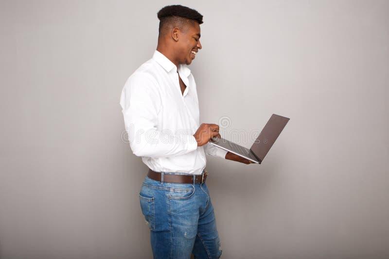 Profil av den lyckliga unga datoren för svart maninnehavbärbar dator vid den gråa väggen royaltyfria foton