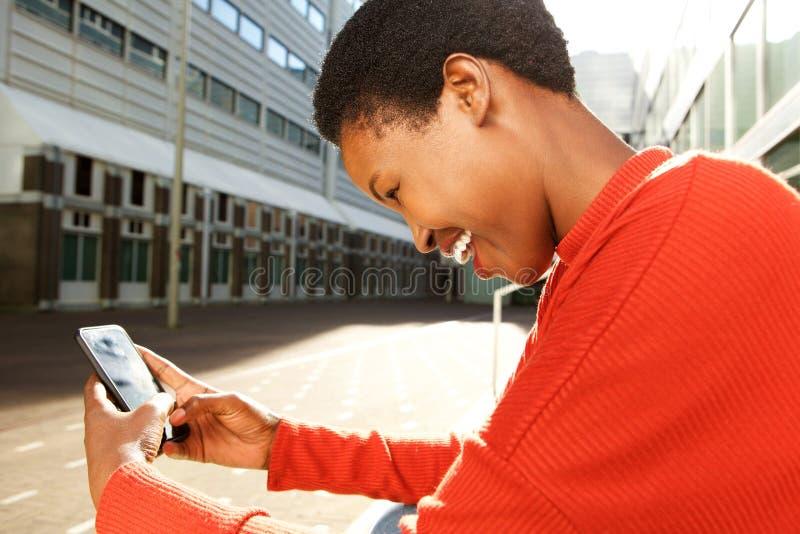 Profil av den lyckliga unga svarta kvinnan som sitter i stad och ser mobiltelefonen royaltyfria bilder