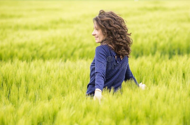 Profil av den unga kvinnan i vetefält arkivbilder