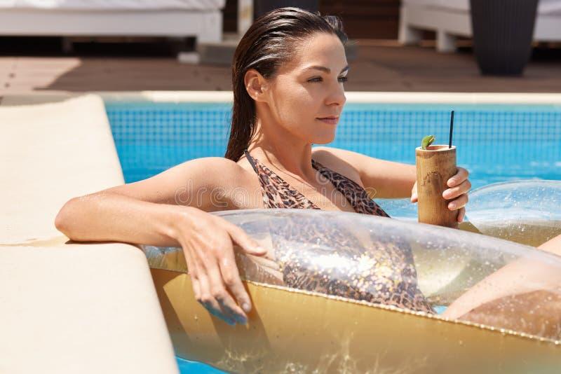 Profil av den unga kvinnan med mörkt vått hår som tycker om på den uppblåsbara badcirkeln som bär i modeswimwear med leopardtryck arkivfoto