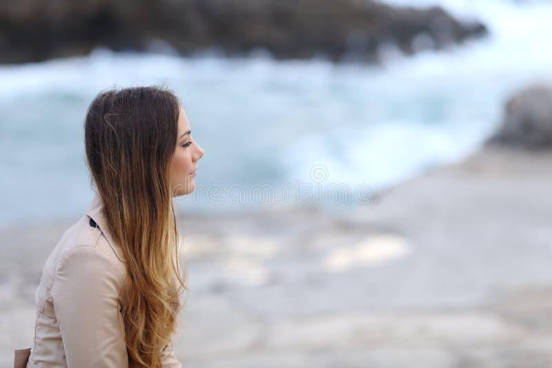 Profil av en eftertänksam kvinna på stranden i vinter royaltyfri fotografi