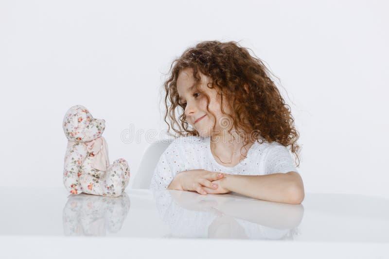 Profil av en gladlynt liten lockig flicka som placeras på en tabell som ser på leksaker, över vit bakgrund arkivbilder