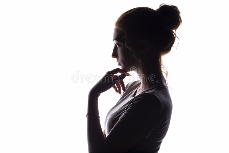 Profil av en härlig flicka med hakahanden som ser föraktfullt in mot, säker ung kvinna på en vit isolerad bakgrund royaltyfri bild
