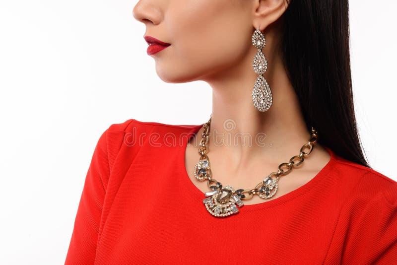 Profil av en härlig kvinna i röd aftonklänning med halsbandet och örhängen arkivbilder