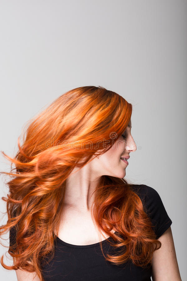 Profil av en kall rödhårig man som snärtar hennes hår arkivfoton