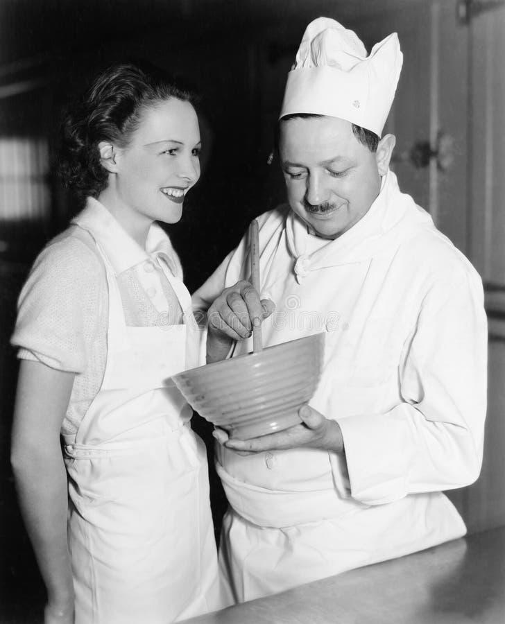 Profil av en kock som rör en blandning i en bunke och ett anseende för ung kvinna bredvid honom (alla visade personer inte är län royaltyfri bild