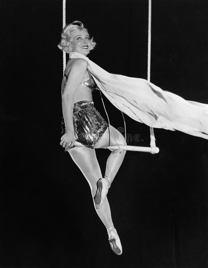 Profil av en kvinnlig cirkusartist som utför på en trapetsstång (alla visade personer inte är längre uppehälle, och inget gods fi royaltyfria foton