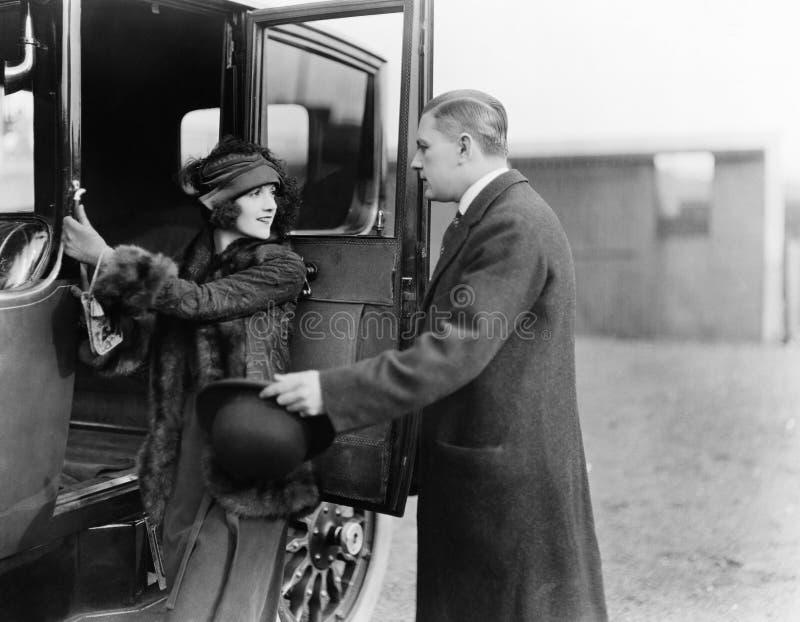 Profil av en man som hjälper en ung kvinna att stiga ombord en bil (alla visade personer inte är längre uppehälle, och inget gods arkivfoto