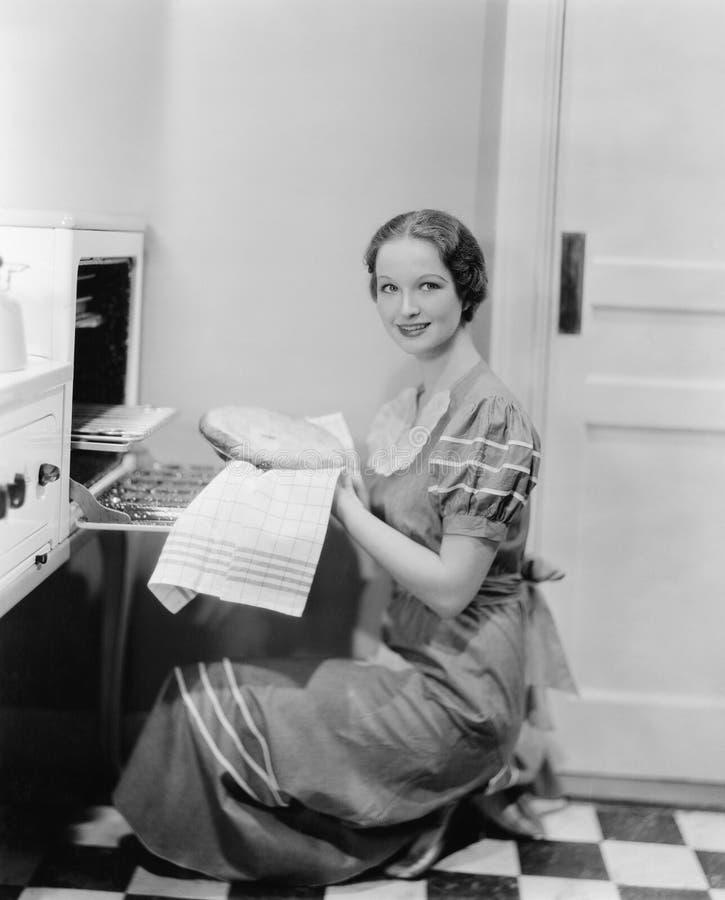 Profil av en ung kvinna som tar en paj ut ur ugnen som ler på kameran (alla visade personer inte är längre uppehälle och inget e arkivbild