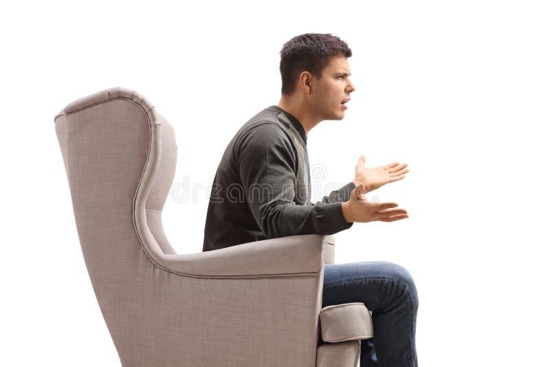 Profil av en ung man som sitter i en fåtölj och argumenterar med någon arkivbilder