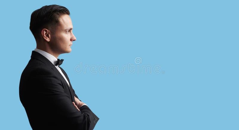 Profil av en ung stilig brunete man i svart dräkt royaltyfria foton