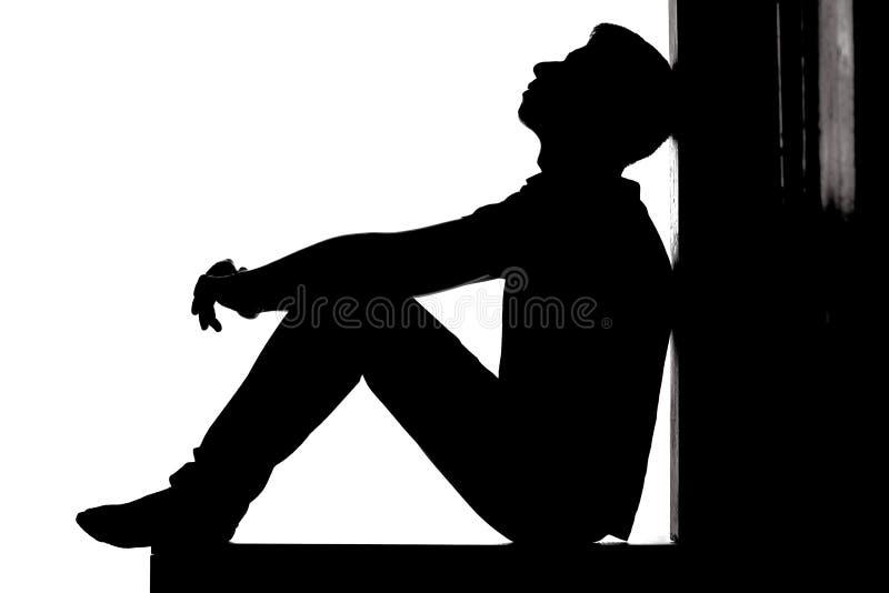 Profil av ett ungt eftertänksamt mansammanträde på golvet och att se upp med hopp och förtvivlan, grabb i fördjupning på vitbaksi royaltyfria foton