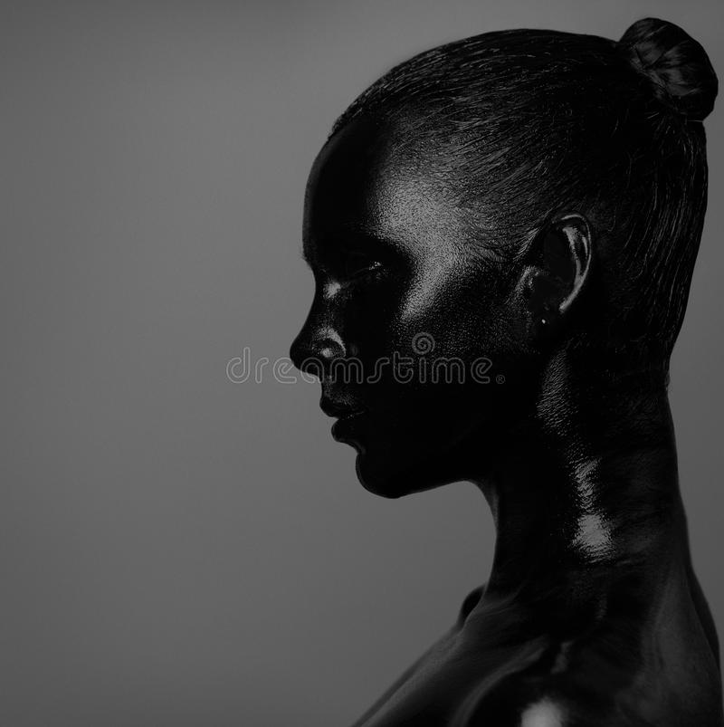 Profil av flickan i svart målarfärg royaltyfri fotografi