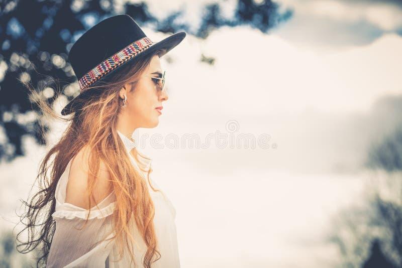 Profil av långt hår för trendig kvinna med hatten och solglasögon royaltyfri foto