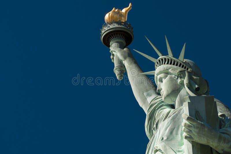 Profil av statyn av frihet mot ljus blå himmel arkivfoton