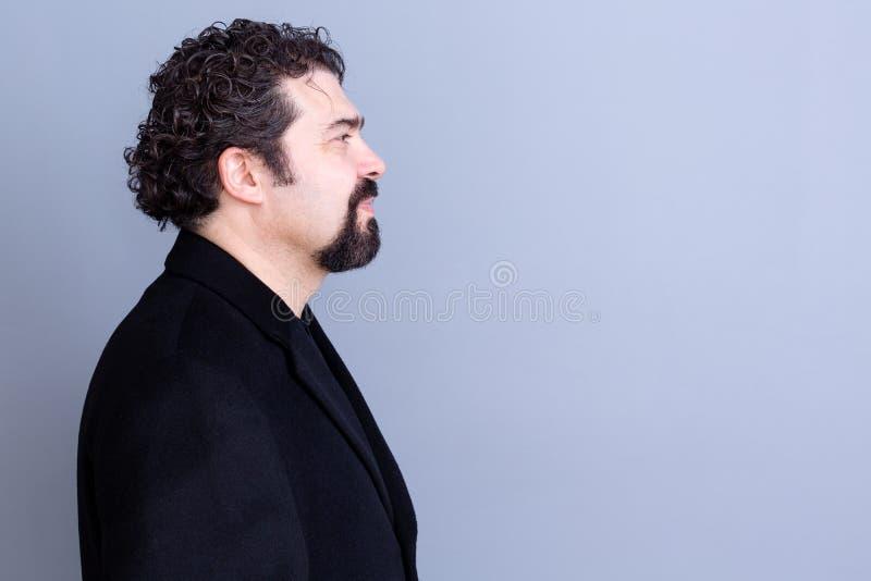 Profil calme d'homme au-dessus de fond gris photo stock