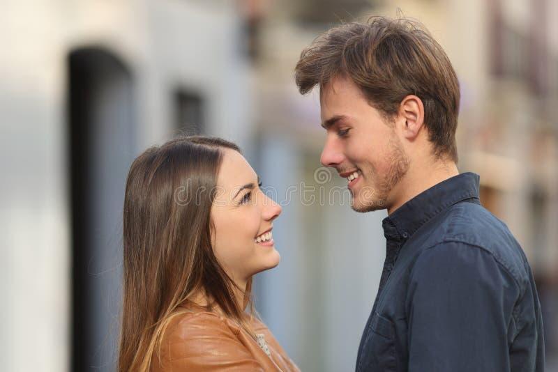 Profil d'un couple se regardant dans la rue image stock