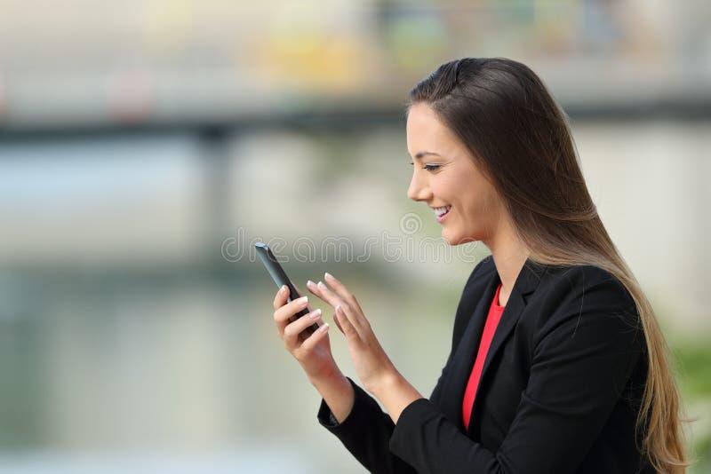Profil d'un exécutif à l'aide d'un téléphone intelligent dehors photographie stock