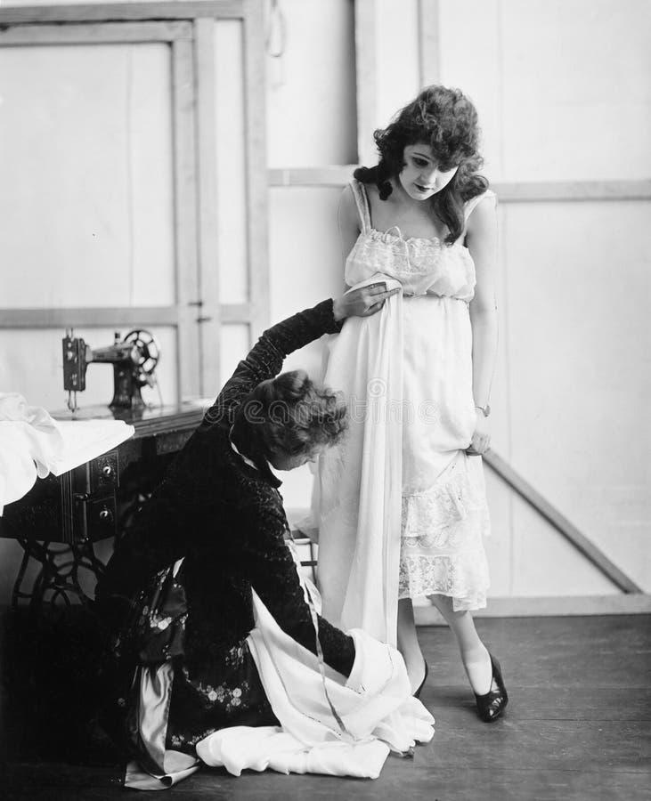 Profil d'un tailleur féminin prenant la mesure d'une jeune femme dans une boutique nuptiale (toutes les personnes représentées ne image libre de droits