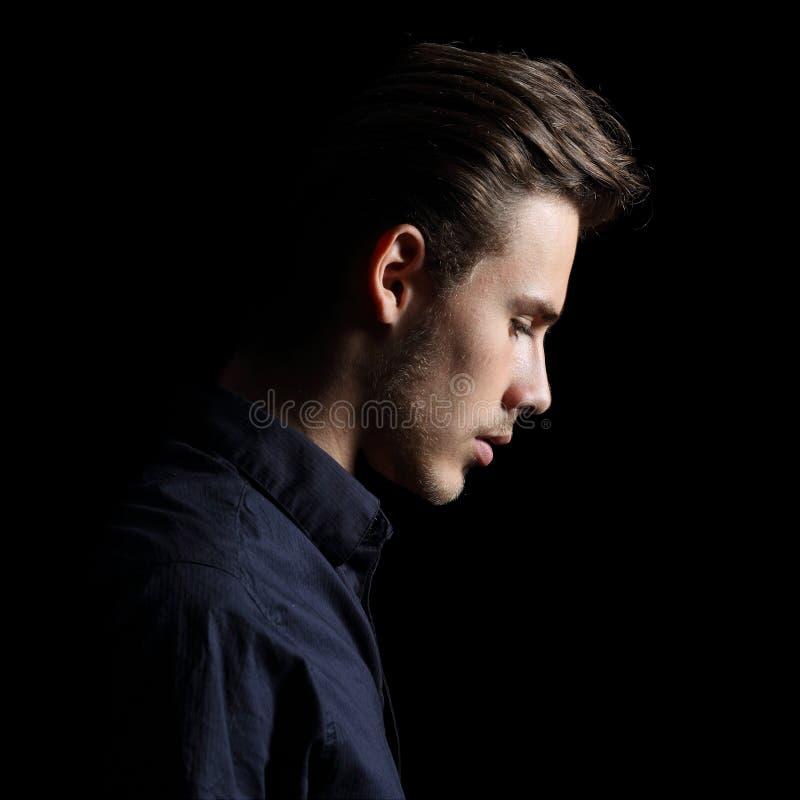 Profil d'un visage triste d'homme découragé sur le noir photo stock