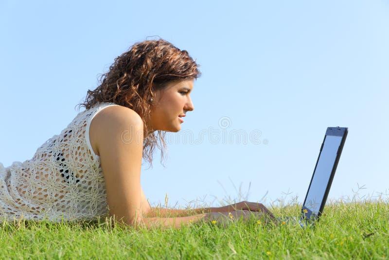 Profil d'une belle femme se trouvant sur l'herbe passant en revue un ordinateur portable photos stock