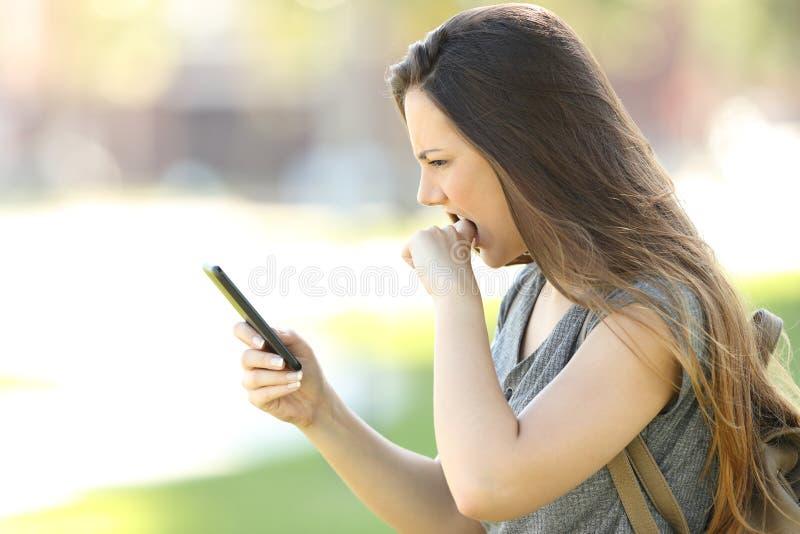 Profil d'une fille fâchée avec le téléphone portable photos stock