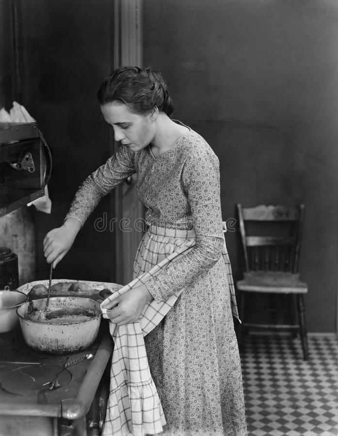 Profil d'une jeune femme faisant cuire la nourriture dans la cuisine (toutes les personnes représentées ne sont pas plus long viv photographie stock libre de droits