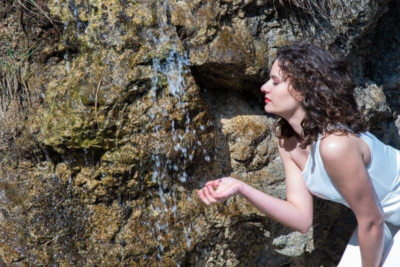 Profil d'une jeune femme qui boit dans une cascade de montagne image stock