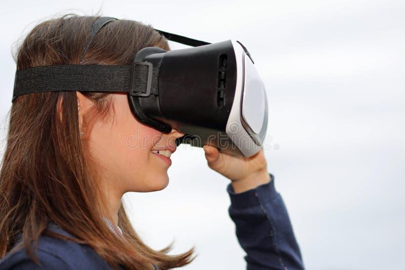 Profil d'une petite fille avec le pare-soleil de VR sur le blanc image libre de droits
