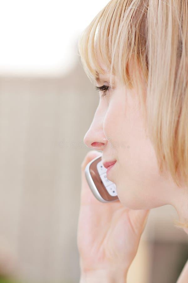 Profil de blonde avec le mobile images stock