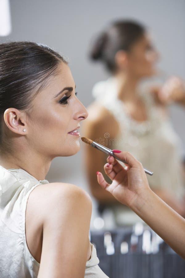 Profil de femme se reposant dans l'application de lustre de lèvre de maquillage photographie stock