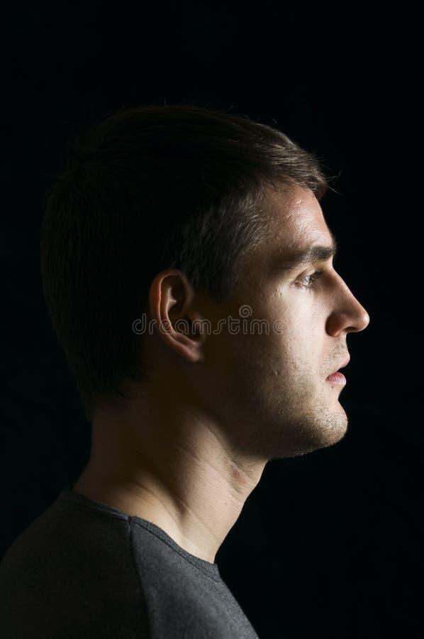 Profil de jeune homme sur le noir photos stock