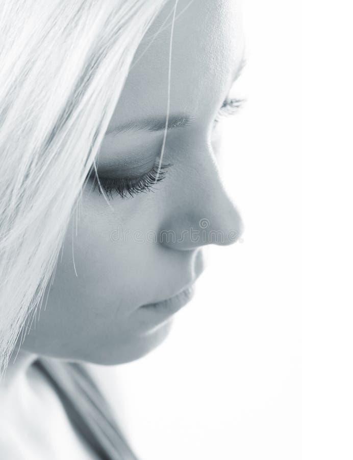 Profil de la belle fille triste dans des sons bleus images stock