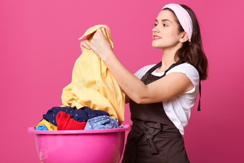 Profil de la brune attrayante avec plaisir tenant la chemise légère après lavage, étant satisfait du résultat, souriant sincèreme photo libre de droits