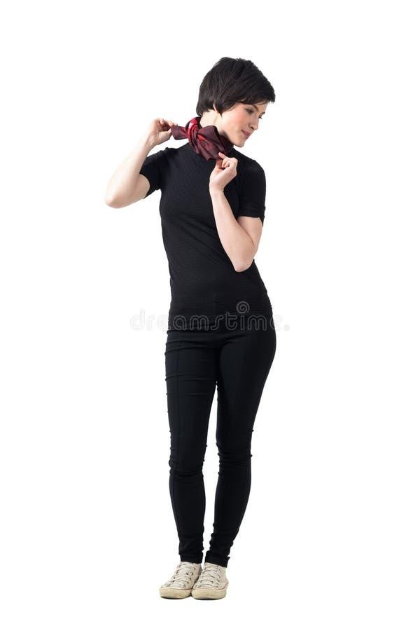 Profil de la jeune brune à la mode mignonne de cheveux courts ajustant le foulard regardant vers le bas image libre de droits