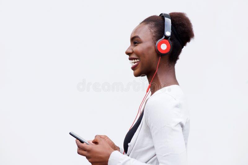 Profil de la jeune femme de couleur heureuse écoutant la musique avec le téléphone et les écouteurs intelligents photo libre de droits