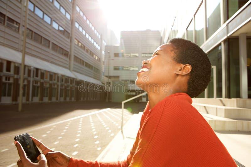 Profil de la jeune femme heureuse d'afro-américain s'asseyant dans la ville et regardant le téléphone portable image libre de droits