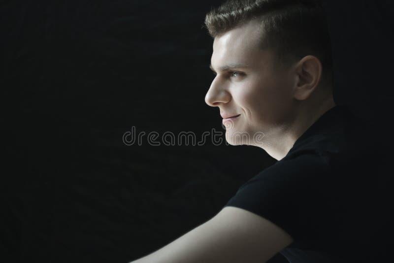 Profil de portrait de sourire de jeune homme dans l'éclairage discret photos stock