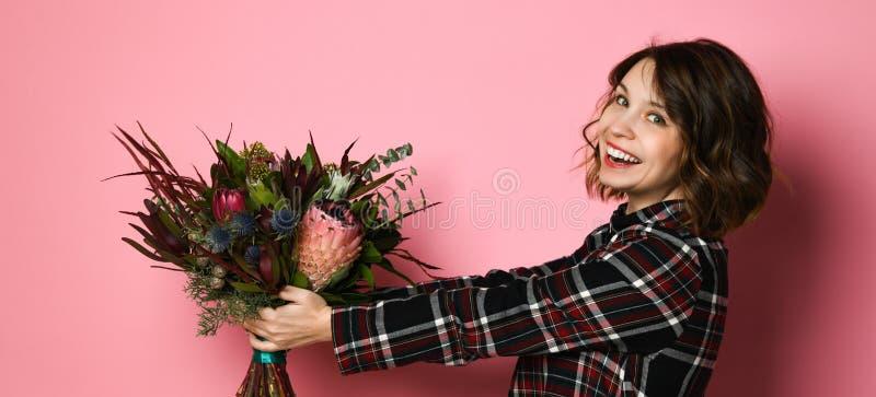 Profil de vue de côté de jeune femme attirante dans un dresst à carreaux foncé tenant le bouquet des fleurs et vous donnant photo libre de droits