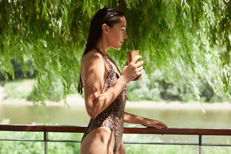 Profil der athletischen schönen vorbildlichen Stellung nahe Ufer, schauend direkter, tragender Leopardschwimmenanzug und lang hab lizenzfreies stockfoto