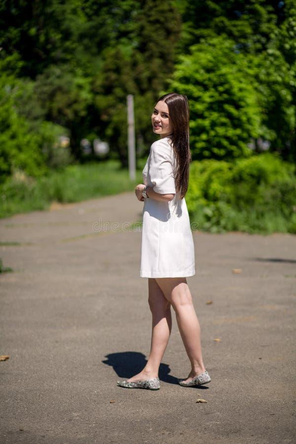 Profil der jungen lächelnden Brunette Frau ist im Park lizenzfreies stockbild