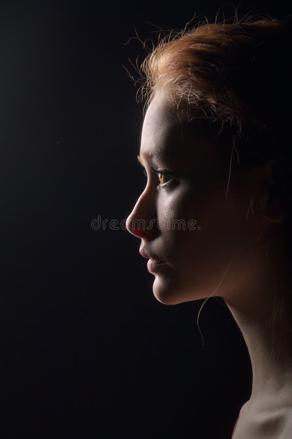 Profil der jungen nachdenklichen Frau stockfotografie