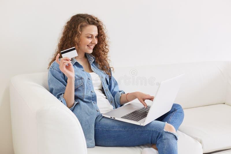 Profil der netten glücklichen jungen Frau mit dem gelockten Haar, das zu Hause, ihren freien Tag online verbringend bleibt und ge stockfotos